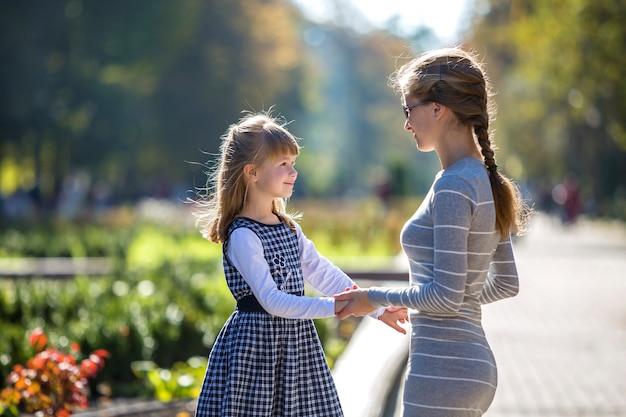 Tylny widok dziecko dziewczyna i matka w sukniach wpólnie trzyma ręki na ciepłym dniu outdoors na pogodnym tle.