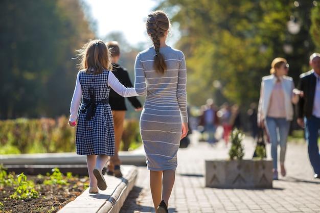 Tylny widok dziecko dziewczyna i matka w sukniach wpólnie trzyma ręki na ciepłym dniu outdoors na pogodnym