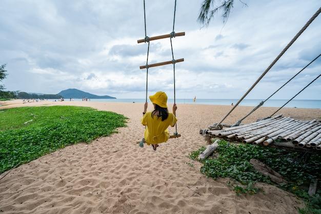 Tylny widok kobieta na huśtawce przy ocean plażą.