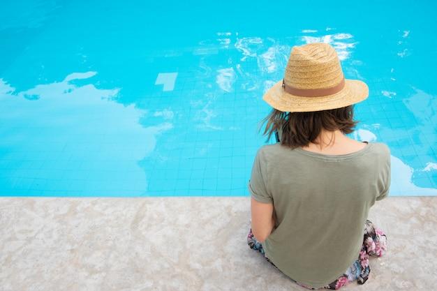 Tylny widok kobieta w lato słomianego kapeluszu obsiadaniu przy poolside