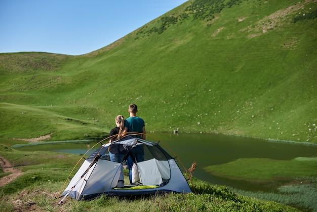 Tylny widok męskiego przytulenia żeński pobliski campingowy patrzejący jezioro przy górami zakrywać z greenery na słonecznym dniu pod niebieskim niebem