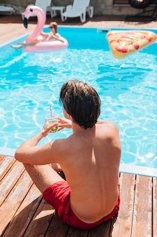 Tylny widok mężczyzna gapi się przy basenem