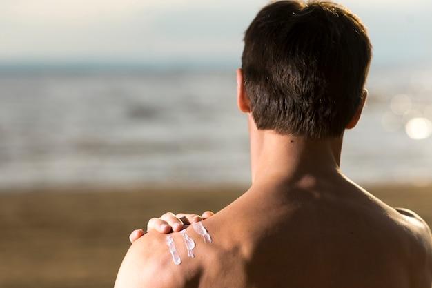 Tylny widok mężczyzna stosuje balsam do ochrony przeciwsłonecznej