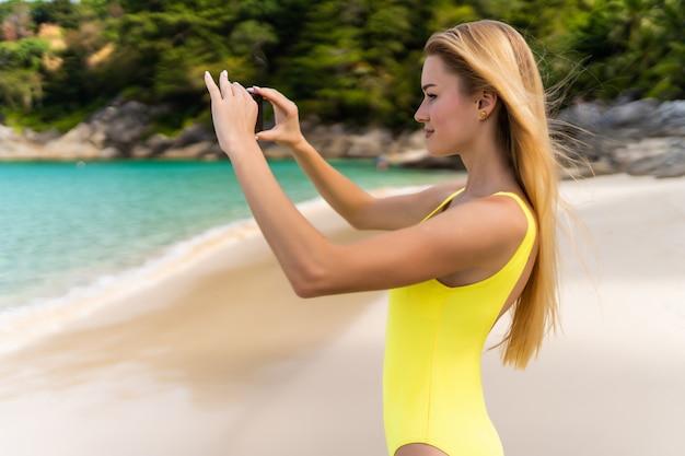 Tylny widok młoda kobieta bierze fotografię z mądrze telefonu aparatem na plaży