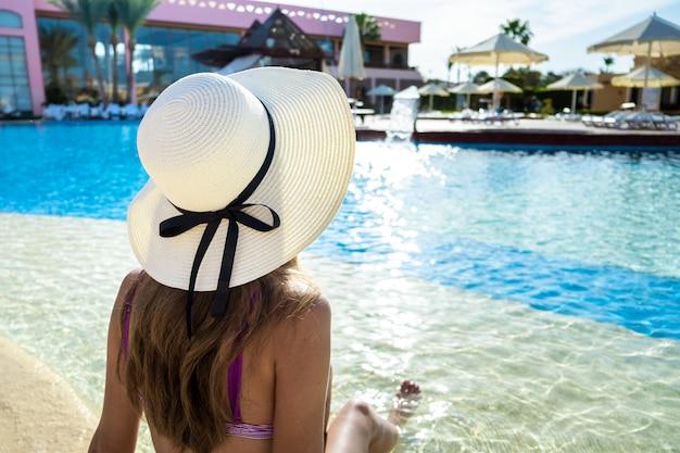 Tylny widok młoda kobieta relaksuje w lecie blisko pływackiego basenu z błękitne wody na słonecznym dniu z długie włosy jest ubranym słomianym kapeluszem.