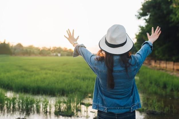 Tylny widok młoda kobieta w kapeluszu. dziewczyna cieszy się przy piękną naturą. podróżuj latem