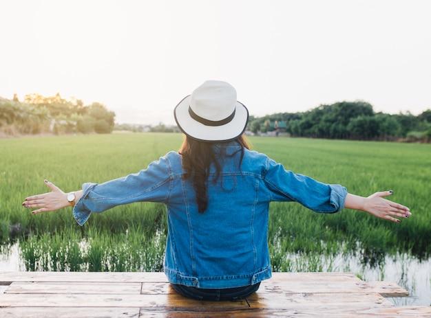 Tylny widok młoda kobieta w kapeluszu. dziewczyna cieszy się przy piękną naturą z zmierzchem. suma podróży