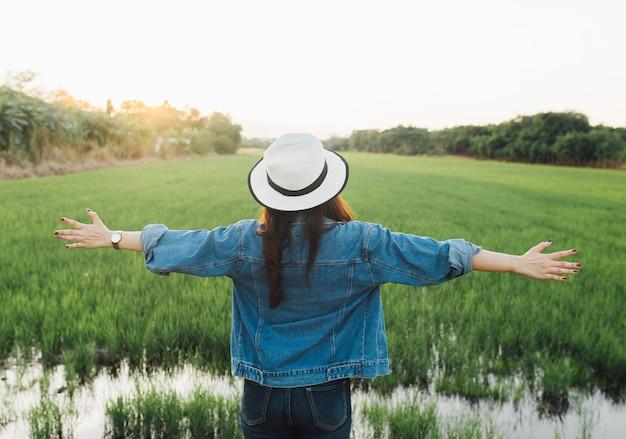 Tylny widok młoda kobieta w kapeluszu. dziewczyna cieszy się przy piękną naturą z zmierzchem.