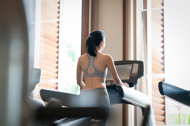 Tylny widok młodej kobiety atlety bieg na karuzeli w gym