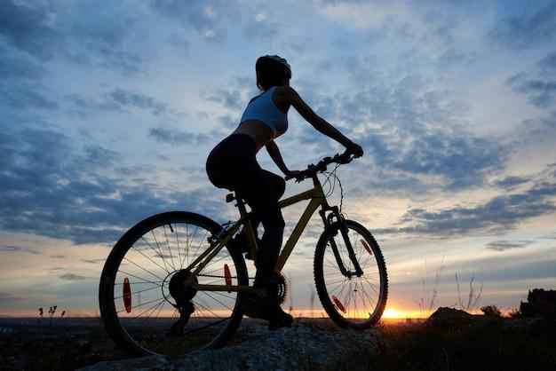 Tylny widok młodej kobiety kolarstwa halny bicykl. sylwetka żeńskiego rowerzysty cieszy się zachód słońca na szczycie góry