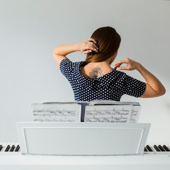 Tylny widok młodej kobiety pozycja za fortepianowym pokazuje tatuażem nad ona z powrotem