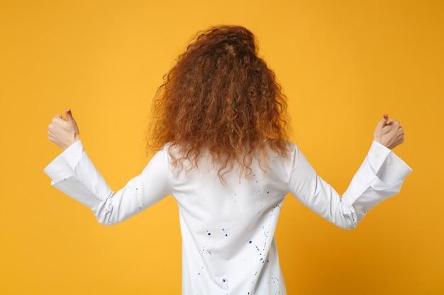 Tylny widok młodej rudej kobiety dziewczyny w dorywczo białej koszuli pozowanie na żółto pomarańczowej ścianie