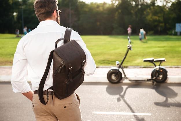 Tylny widok młody człowiek z plecakiem pozuje blisko nowożytnego motocyklu outdoors