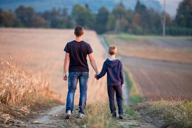 Tylny widok młody ojciec i syn chodzi wpólnie trzymający ręki trawiastym polem na zamazanych mgłowych zielonych drzewach i niebieskim niebie