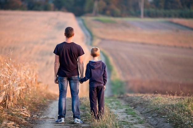 Tylny widok młody ojciec i syn chodzi wpólnie trzymający ręki trawiastym polem na zamazanych mgłowych zielonych drzewach i niebieskim niebie.