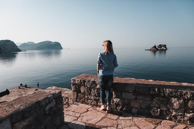 Tylny widok myśleć samotnie i ogląda morze z horyzontem w tle kobieta, montenegro