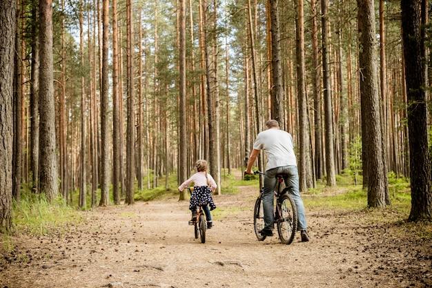 Tylny widok ojca i córki jeździeccy bicykle wokoło lasu młoda rodzina w lata kolarstwie w parku temat rodzina bawi się plenerowego odtwarzanie przygoda czasu wolnego pojęcie.