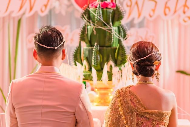 Tylny widok panny młodej i pana młodego w ceremonii ślubnej w stylu tajskim.