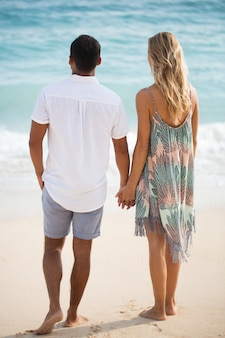 Tylny widok para trzyma się za ręce na plaży