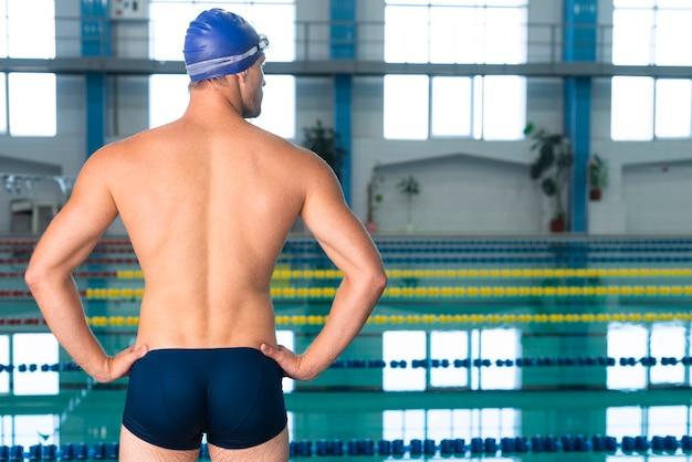 Tylny widok patrzeje pływackiego basenu mężczyzna