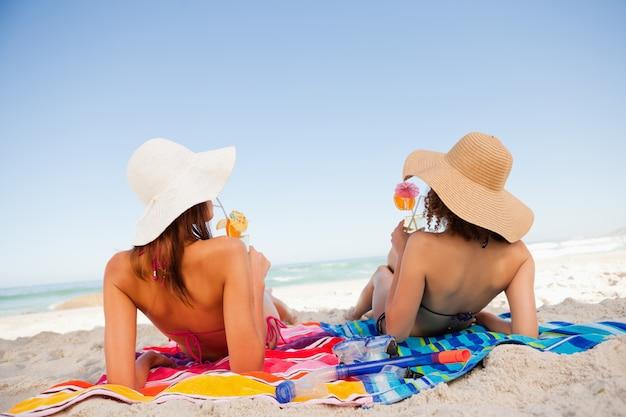 Tylny widok piękne kobiety sunbathing podczas gdy sączysz koktajle na plaży