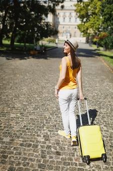 Tylny widok podróżnik turystyczny kobieta w żółtych ubraniach casual, kapelusz z walizką, patrząc na bok spaceru w mieście na świeżym powietrzu. dziewczyna wyjeżdża za granicę na weekendowy wypad. styl życia podróży turystycznej.
