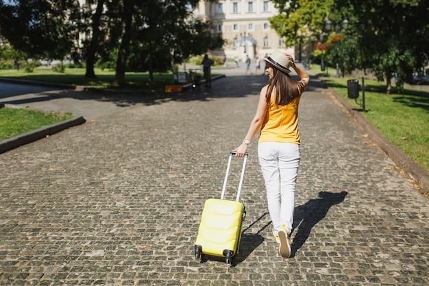 Tylny widok podróżnik turystyczny kobieta w żółtym letnim kapeluszu dorywczo ubrania z walizką spaceru w mieście na świeżym powietrzu. dziewczyna wyjeżdża za granicę na weekendowy wypad. koncepcja życia podróż turystyka.