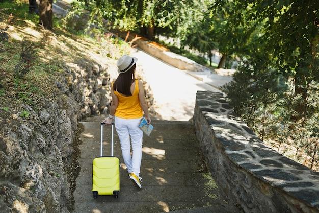 Tylny widok podróżnik turystyczny kobieta w żółtym letnim kapeluszu na co dzień ubrania z mapą miasta walizka chodzenie po mieście na świeżym powietrzu. dziewczyna wyjeżdża za granicę na weekendowy wypad. styl życia podróży turystycznej.