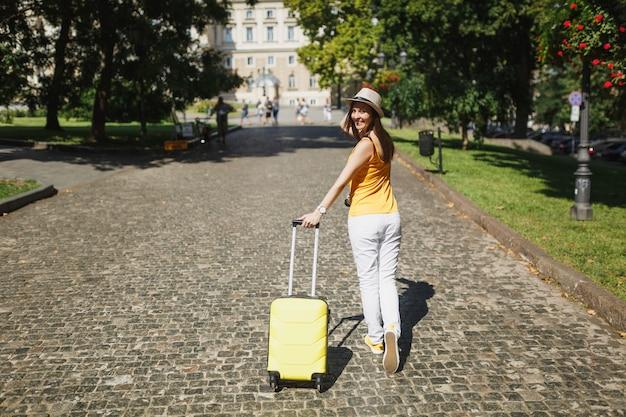 Tylny widok podróżnika turystycznego kobiety w żółtym letnim kapeluszu dorywczo ubrania z walizką spaceru rozglądając się w mieście na świeżym powietrzu. dziewczyna wyjeżdża za granicę na weekendowy wypad. styl życia podróży turystycznej.
