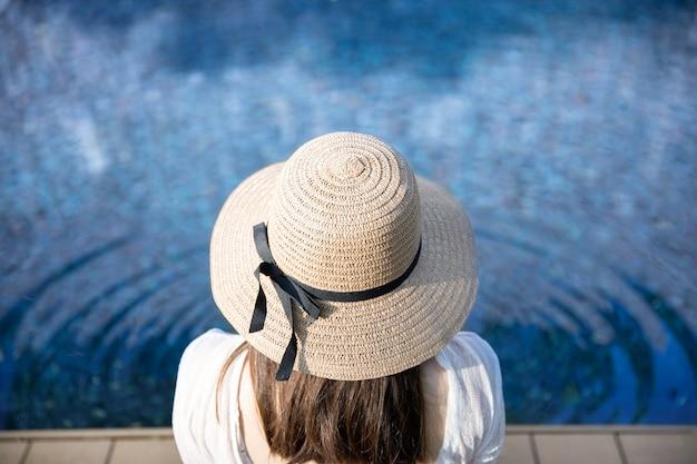 Tylny widok relaksująca kobieta w swimsuit i słomianym kapeluszu siedzi blisko swimmingpool