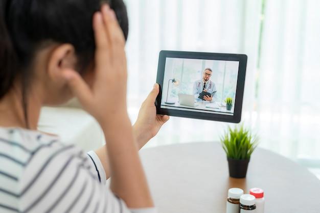 Tylny widok robi wideo rozmowie z jej lekarką z jej lekarką z jej czuciową migreną młoda kobieta na cyfrowej pastylki opieki zdrowotnej technologii cyfrowej technologii online konsultaci podczas gdy zostający w domu.