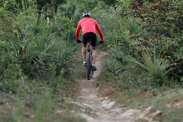 Tylny widok rowerzysty jadącego wąską ścieżką w tropikalnym lesie, w kasku rowerowym i czerwonej koszulce rowerowej.