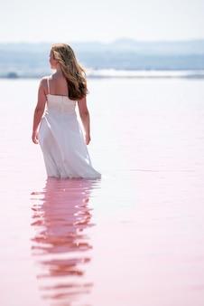 Tylny widok śliczna nastolatek kobieta jest ubranym biel smokingową pozycję na zadziwiającym różowym jeziorze