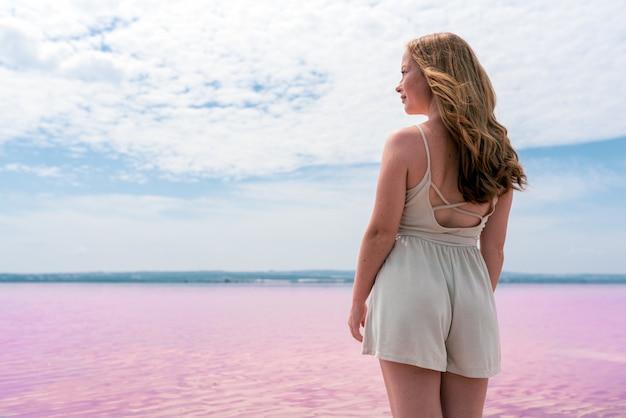 Tylny widok śliczna nastolatek kobieta jest ubranym lato odziewa na różowym jeziorze