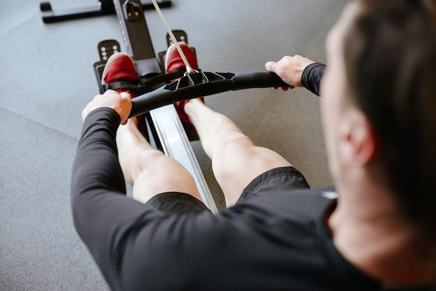 Tylny widok sportowy mężczyzna używa wioślarską maszynę