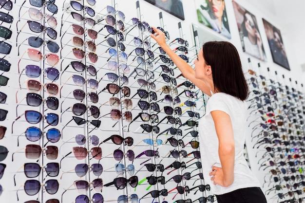 Tylny widok sprawdza okulary przeciwsłonecznych kobieta