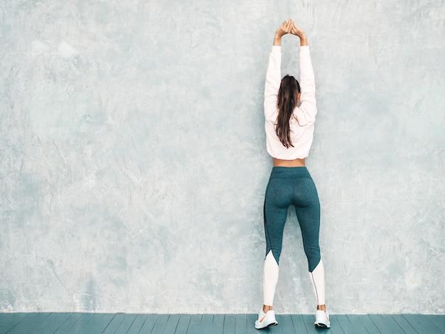 Tylny widok sprawności fizycznej kobieta odziewa ufny w sportach. kobieta rozciąga out przed trenować blisko szarości ściany w studiu