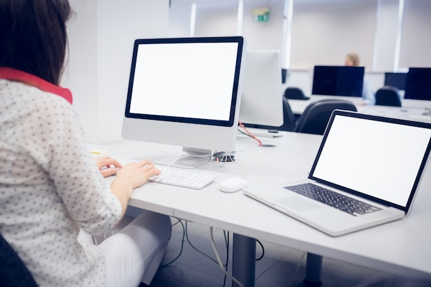 Tylny widok studencki używa komputer przy uniwersytetem