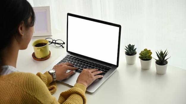 Tylny widok szczęśliwej młodej kobiety freelancer pracuje i pisze sms-y na laptopie.