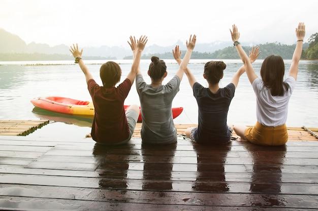 Tylny widok szczęśliwi młodzi przyjaciele siedzi na tratwie i ma cieszyć się słonecznego dzień. koncepcja podróży.