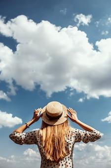 Tylny widok szczupła młoda kobieta w modnym słomianym kapeluszu. romantyczna dziewczyna w białej sukni chodzi i marzy na przestronnym polu. zielone pole w słoneczną pogodę.