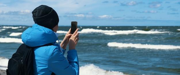 Tylny widok turysty dziewczyna robi zdjęcie aparatem cyfrowym telefonu komórkowego