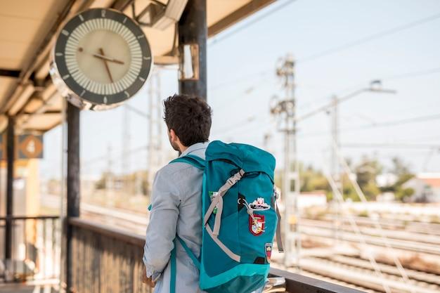 Tylny widoku podróżnik patrzeje zegar
