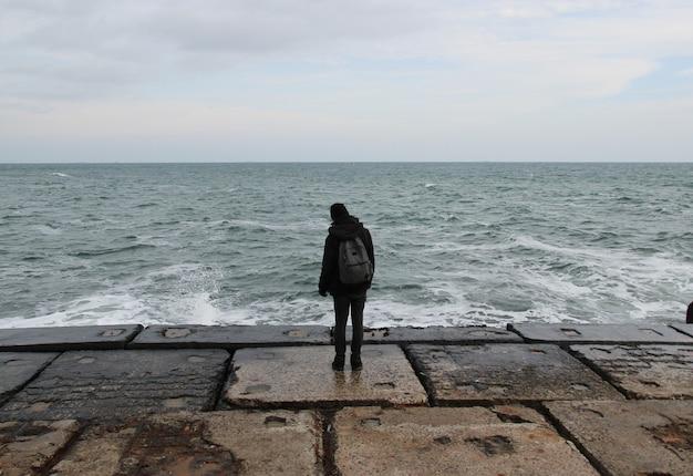 Tylny widoku portret młody człowiek pozycja przeciw morzu na wielkim betonowym molu z dużym falowym biciem