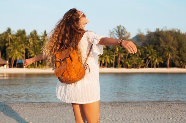 Tyłu pięknej kobiety w białej sukni spacerującej beztrosko na tropikalnej plaży ze skórzanym plecakiem.