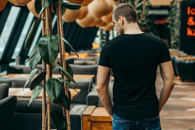 Tyłu stylowa blondynka na sobie czarną koszulkę pozowanie w studio