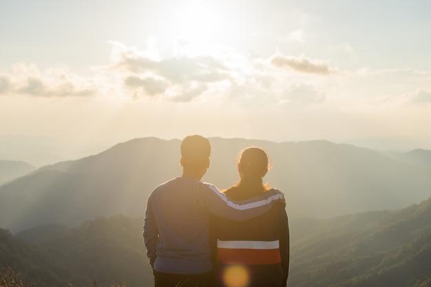 Tyły pary miłości stojak na odgórnym przyglądającym widoku z mgłą i chmurą.