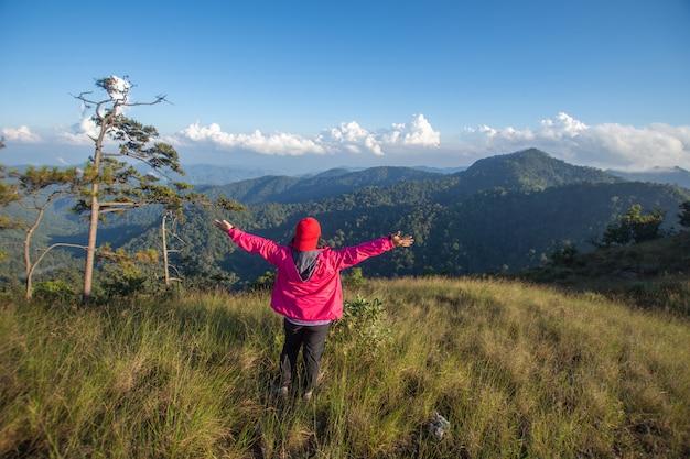 Tyły szczęśliwy kobieta stojak na odgórnym halnym przyglądającym widoku z mgłą i chmurą przy doi langka luang, chiang raja prowincja. nieostrość.