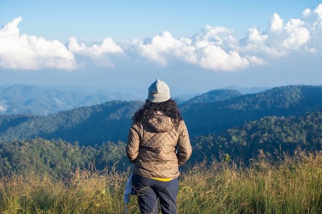 Tyły szczęśliwy kobieta stojak na odgórnym halnym przyglądającym widoku z mgłą i chmurą.