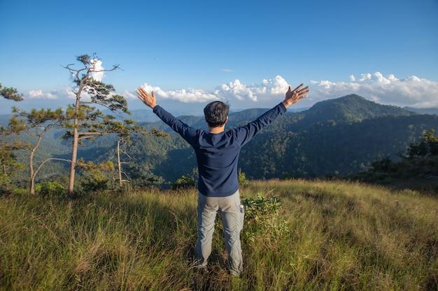 Tyły szczęśliwy mężczyzna stojak na odgórnym halnym przyglądającym widoku z mgłą i chmurą przy doi langka luang, chiang raja prowincja. nieostrość.